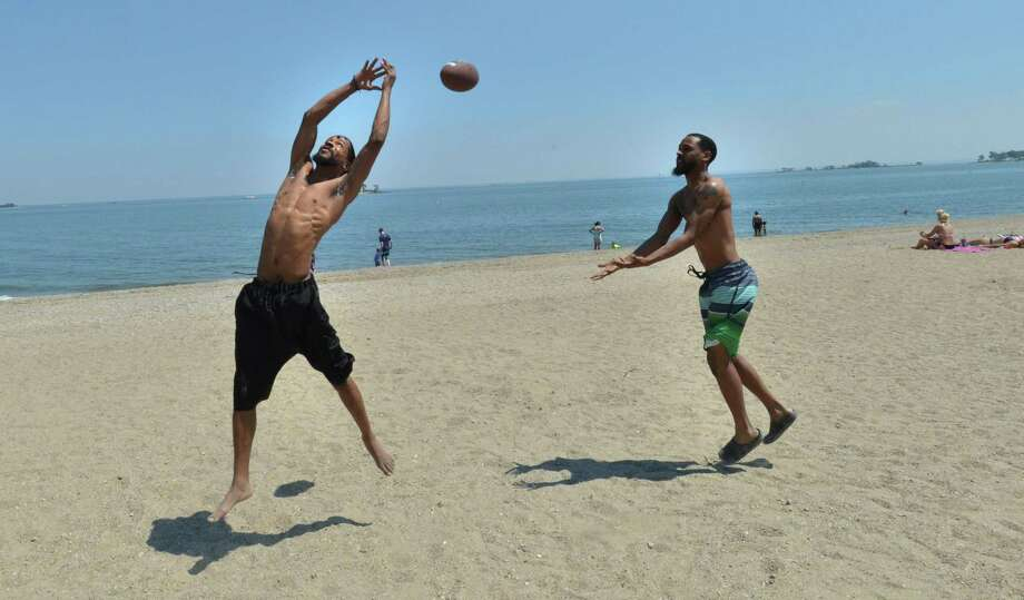 Terrance and Travis Fullmore enjoy a game of football during temperatures in the nineties on Monday June 12, 2017 at Calf Pasture beach in Norwalk Conn. Photo: Alex Von Kleydorff / Hearst Connecticut Media / Norwalk Hour