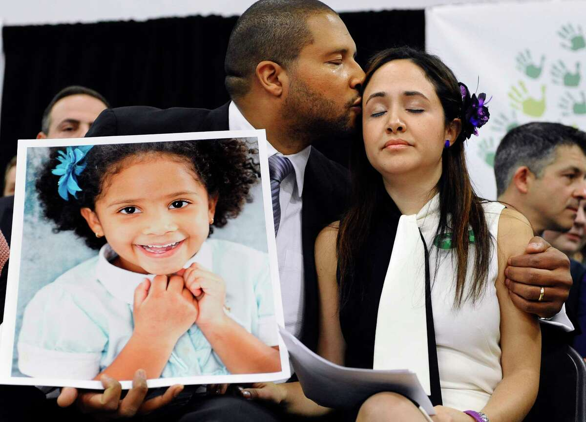 FILE - In this Jan. 14, 2013, file photo, Jimmy Greene, left, kisses his wife Nelba Marquez-Greene while holding a portrait of their daughter, Sandy Hook Elementary School shooting victim Ana Marquez-Greene, at a news conference at Edmond Town Hall in Newtown, Conn. Ana Marquez-Greene was one of 26 people killed in a shooting massacre at the school on Dec. 14, 2012, in Newtown, Conn. Nelba Marquez-Greene is among the families of some shooting victims angered by a planned NBC television interview by Megyn Kelly scheduled to air Sunday, June 18, 2017, with Alex Jones, who has claimed the 2012 massacre never happened. (AP Photo/Jessica Hill, File)