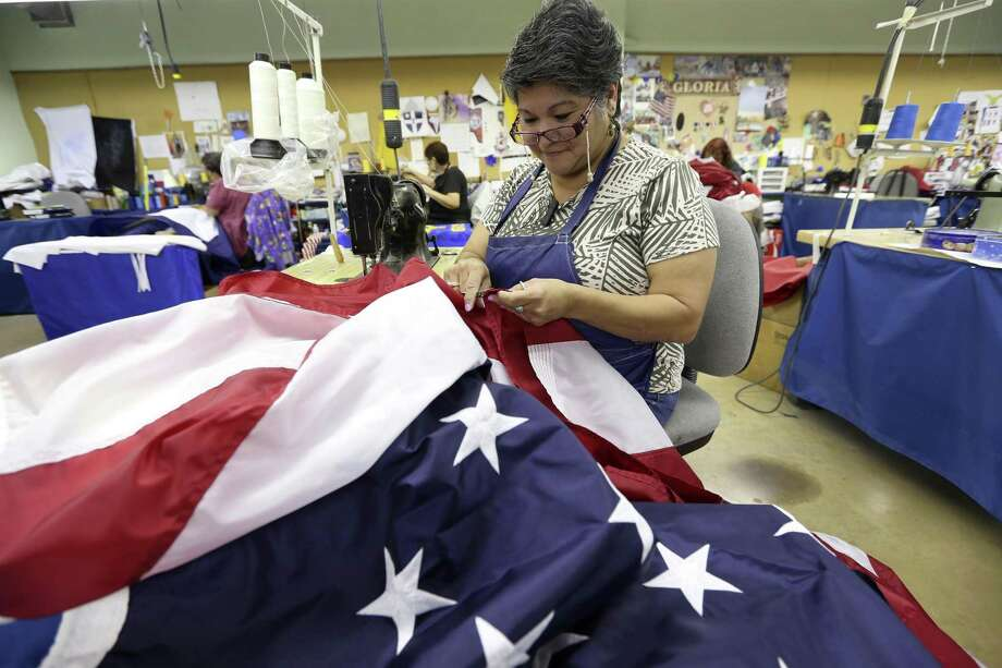 Dixie Flag & Banner employee Lucy Rodriguez trims small threads off an American flag produced at the San Antonio-based flag manufacturer. Dixie Flag & Banner has a team of 10 seamsters. Photo: William Luther /San Antonio Express-News / © 2017 San Antonio Express-News