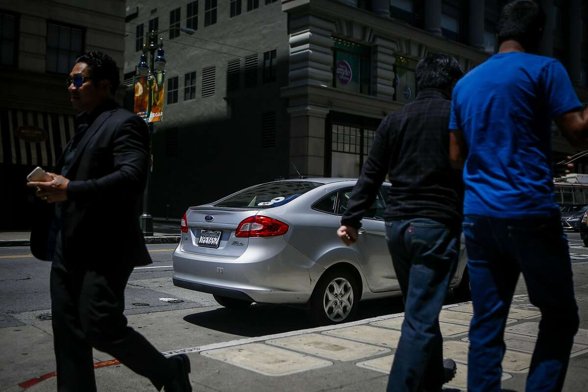 Pedestrians walk past an Uber car in downtown San Francisco on June 12, 2017.