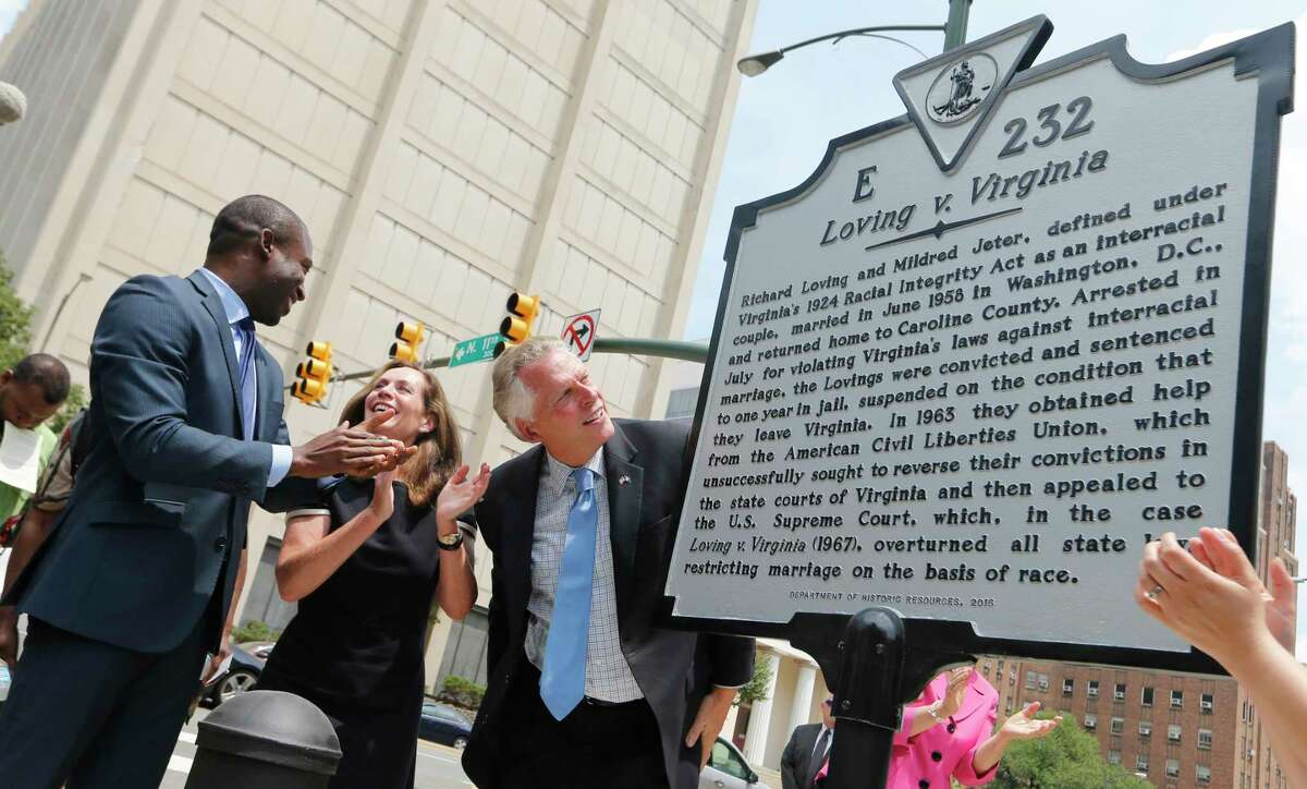 Virginia Gov. Terry McAuliffe , right, looks over a marker that commemorates the 50th anniversary of the end of the ban on interracial marriage.