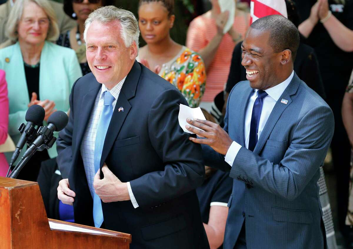 Virginia Gov. Terry McAuliffe, left, shares a laugh with Richmond mayor, Levar Stoney, right during a ceremony to unveil a historical marker commemorating the 50th anniversary of the U.S. Supreme Court decision that struck down bans on interracial marriage Monday, June 12, 2017, in Richmond, Va. The new historical marker to commemorate the lawsuit brought by Richard and Mildred Loving, was dedicated outside the old Virginia Supreme Court, which ruled against the Lovings before they ultimately won in the U.S. Supreme Court. (AP Photo/Steve Helber)
