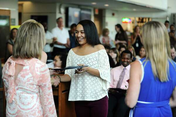 Armani Moore, center, shakes hands with school counselor Mairead Collins after receiving her diploma during the Alternative Routes to Success graduation ceremony in Government Center in Stamford, Conn. on Monday, June 12, 2017.