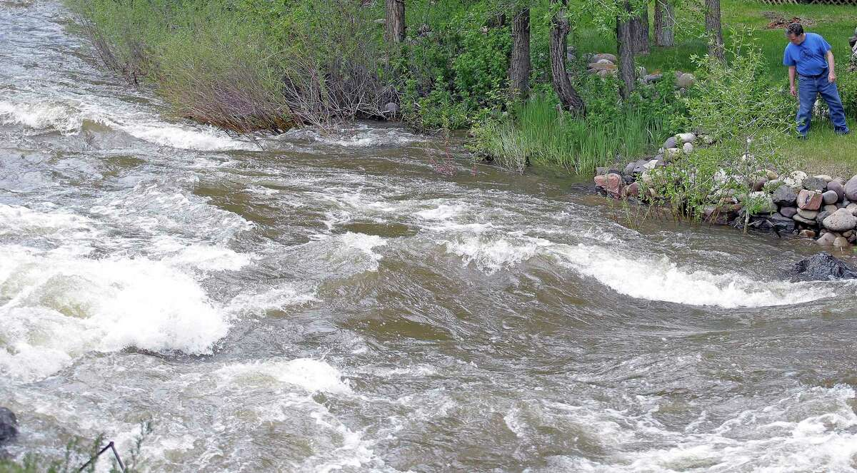 Last month, Ron Lenfield watches the fast-flowing Weber River along his property, in Utah, where rivers are expected to remain dangerously swollen.
