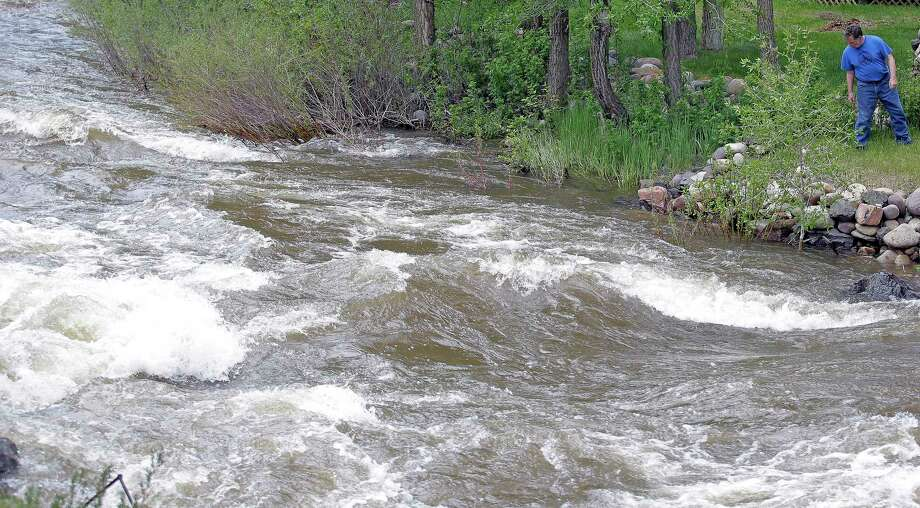Last month, Ron Lenfield watches the fast-flowing Weber River along his property, in Utah, where rivers are expected to remain dangerously swollen. Photo: Rick Bowmer, STF / Copyright 2017 The Associated Press. All rights reserved.