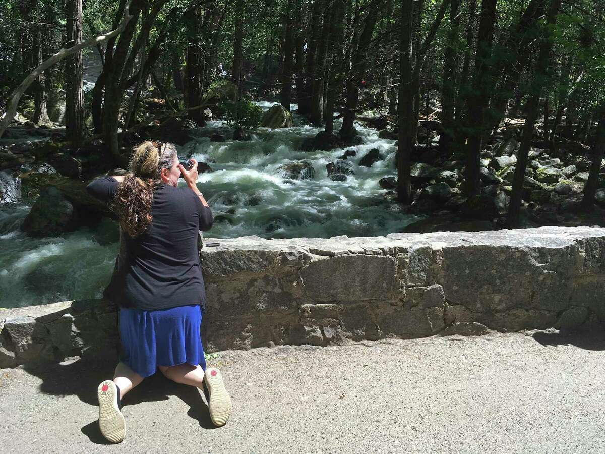 In this photo taken May 25, 2017, a woman braces herself at Yosemite National Park, Calif., while photographing a rushing creek below Bridalveil Fall. Officials fear a surge in drownings following record snowfall this winter as the weather heats up in California and other U.S. western states. Several drownings have already been reported in frigid, swift rivers that are popular for swimming, whitewater rafting and fishing. (AP Photo/Scott Smith)