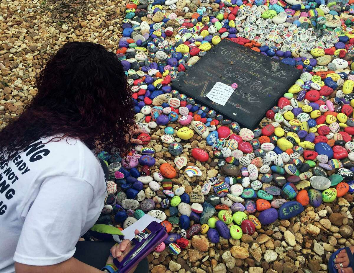 Lizbeth DaVila looks over the rocks painted with inspirational messages at the
