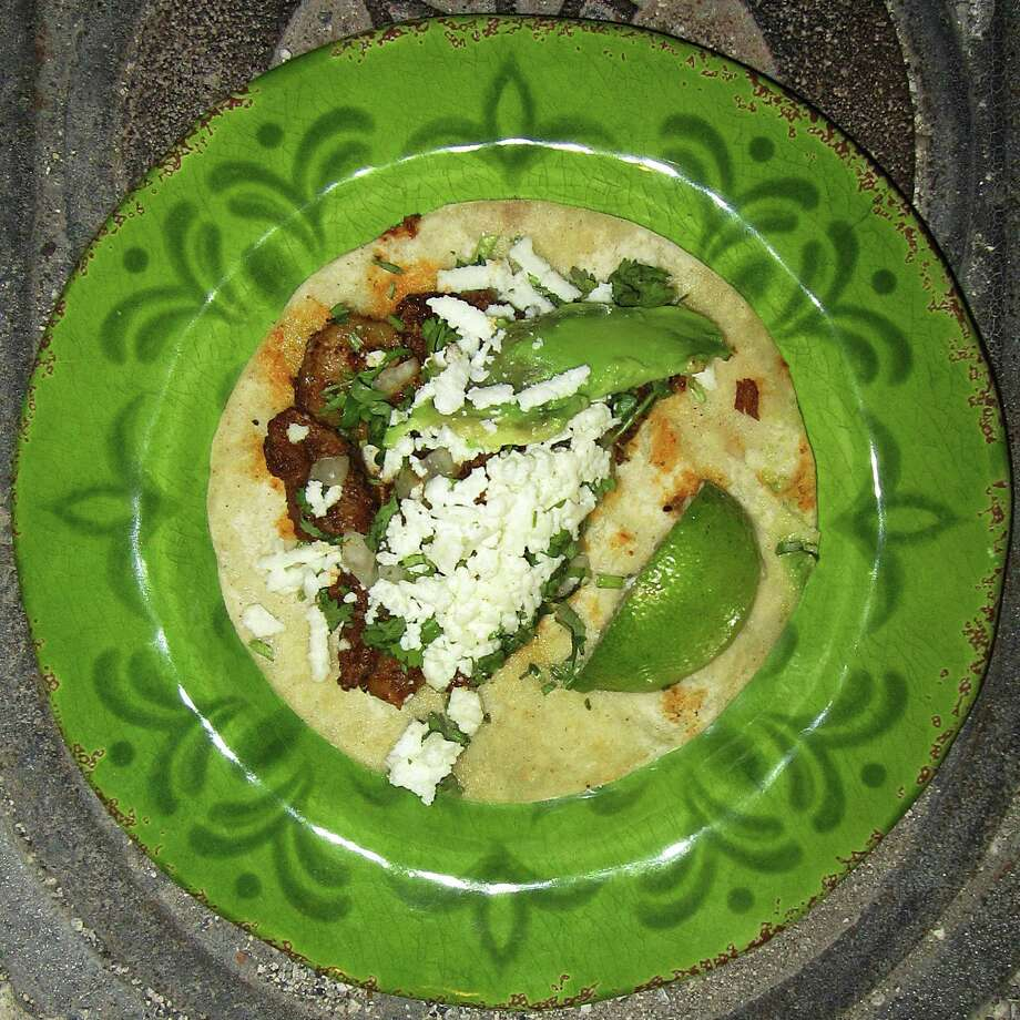 Al pastor taco with onions, cilantro, cheese and avocado on a commercial corn tortilla from the Tacos El Regio trailer outside Hardbodies male strip club. Photo: Mike Sutter /San Antonio Express-News
