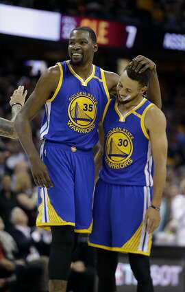 Golden State Warriors' Kevin Durant (35) hugs teammate Stephen Curry (30) during the first half of Game 4 of basketball's NBA Finals against the Cleveland Cavaliers in Cleveland, Friday, June 9, 2017. (AP Photo/Tony Dejak)