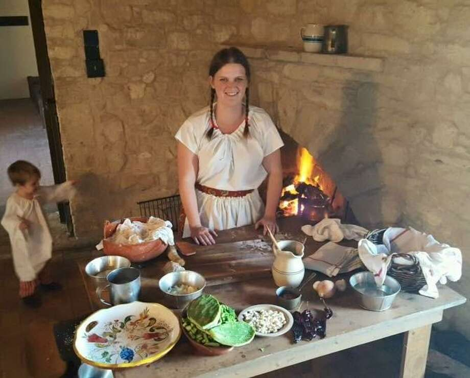 Amanda Maloney, a Texas historical re-enactor based in Pipe Creek who specializes in the 1830s-60s, displays food that was served during that era. Indoor hearths were often used to long-simmer foods. Photo: Courtesy Photo
