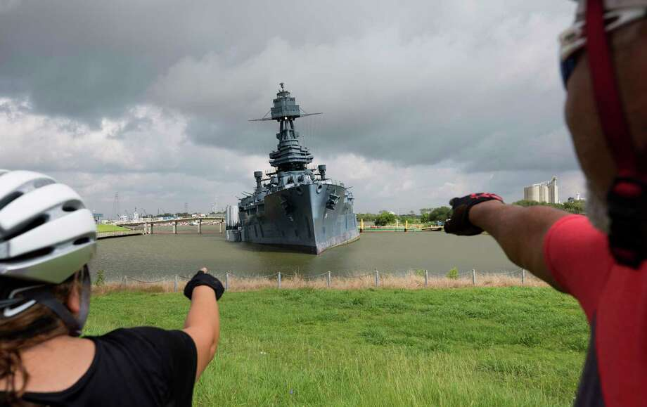 Sara and Javier Montoya stop for a view of the 103-year-old Battleship Texas on Monday. Workers are trying to correct the ship's tilt. Photo: Godofredo A. Vasquez, Staff / Godofredo A. Vasquez
