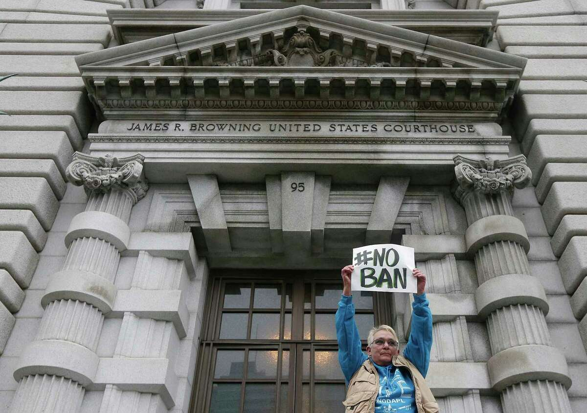 FILE--In this Feb. 7, 2017, file photo, Karen Shore holds up a sign outside of the 9th U.S. Circuit Court of Appeals in San Francisco, Calif. A ruling Monday, June 12, 2017, from a unanimous three-judge panel of the 9th U.S. Circuit Court of Appeals deals the administration another legal defeat as the Supreme Court considers a separate case on the issue. (AP Photo/Jeff Chiu, file)