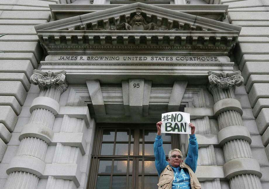 FILE--In this Feb. 7, 2017, file photo, Karen Shore holds up a sign outside of the 9th U.S. Circuit Court of Appeals in San Francisco, Calif. A ruling Monday, June 12, 2017, from a unanimous three-judge panel of the 9th U.S. Circuit Court of Appeals deals the administration another legal defeat as the Supreme Court considers a separate case on the issue. (AP Photo/Jeff Chiu, file) Photo: Jeff Chiu, STF / Copyright 2017 The Associated Press. All rights reserved.
