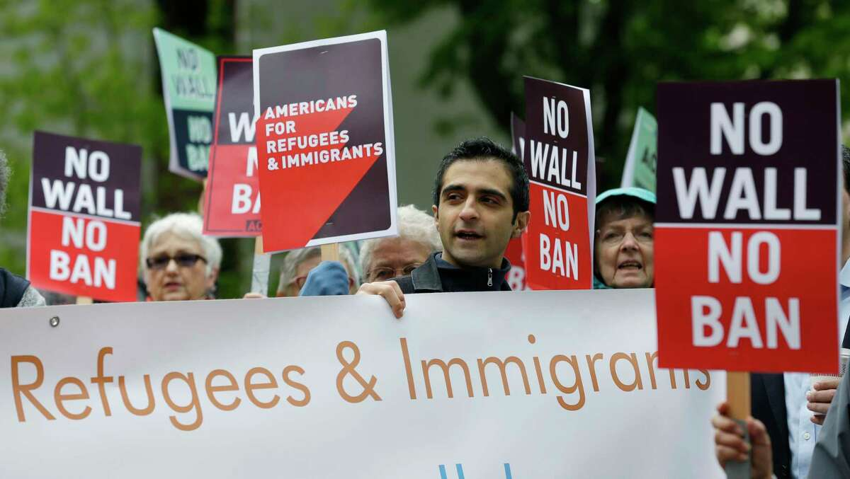 FILE--In this May 15, 2017, file photo, protesters hold signs during a demonstration against President Donald Trump's revised travel ban, Monday, May 15, 2017, outside a federal courthouse in Seattle. A three-judge panel of the 9th U.S. Circuit Court of Appeals on Monday upheld a decision to block the revised travel ban, which would suspend the nation's refugee program and temporarily bar new visas for citizens of Iran, Libya, Somalia, Sudan, Syria and Yemen. (AP Photo/Ted S. Warren, file)