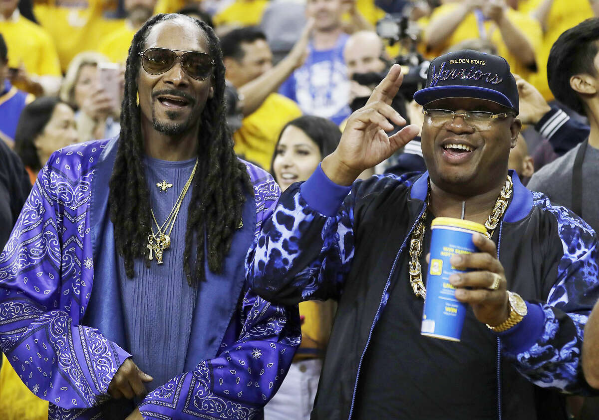 FILE - Musicians Snoop Dogg, left, and E-40 pose for photos before Game 5 of basketball's NBA Finals between the Golden State Warriors and the Cleveland Cavaliers in Oakland, Calif., Monday, June 12, 2017.