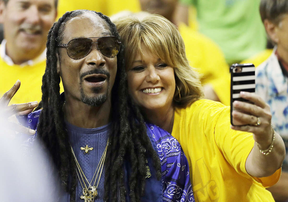 FILE - Musician Snoop Dogg, left, poses with a fan for photos before Game 5 of basketball's NBA Finals between the Golden State Warriors and the Cleveland Cavaliers in Oakland, Calif., Monday, June 12, 2017.