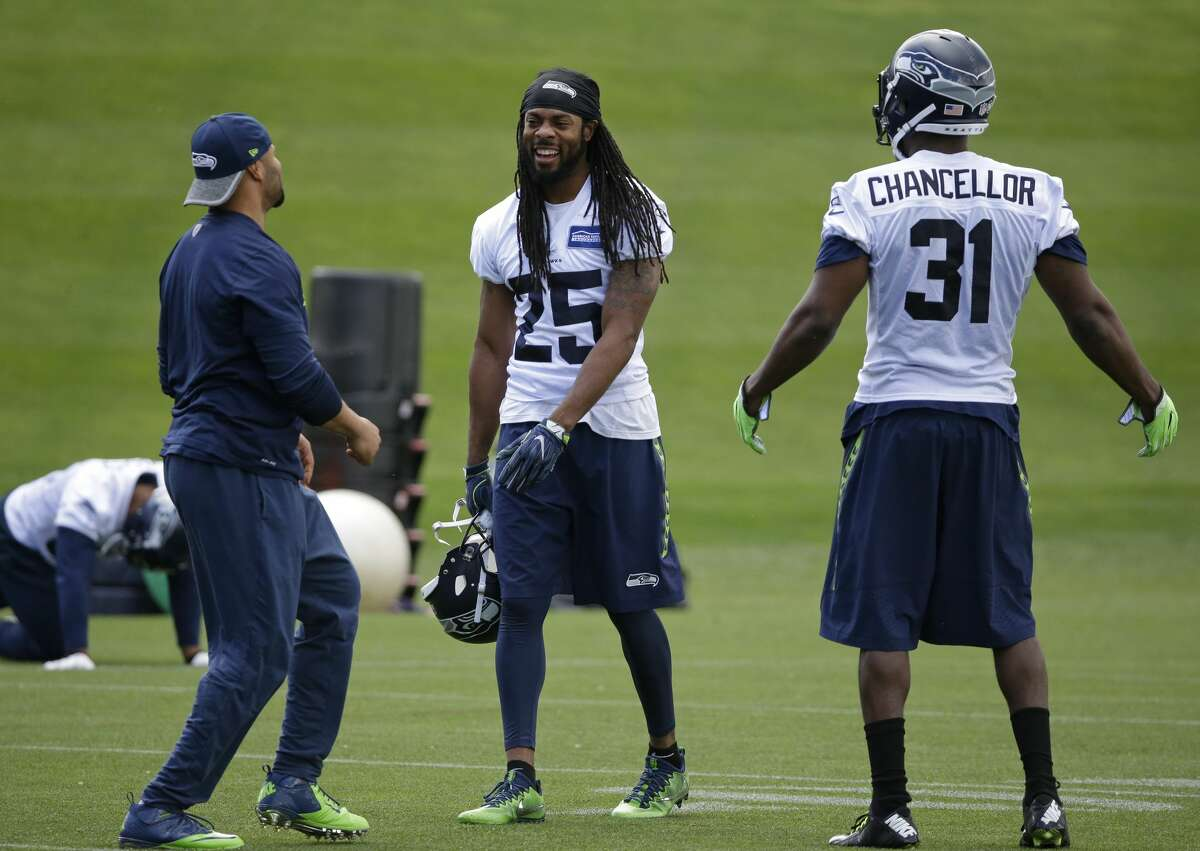 Seattle Seahawks strong safety Kam Chancellor (31) and cornerback Richard Sherman (25) talk with defensive coordinator Kris Richard left, during NFL football practice, Friday, June 9, 2017, in Renton, Wash. (AP Photo/Ted S. Warren)