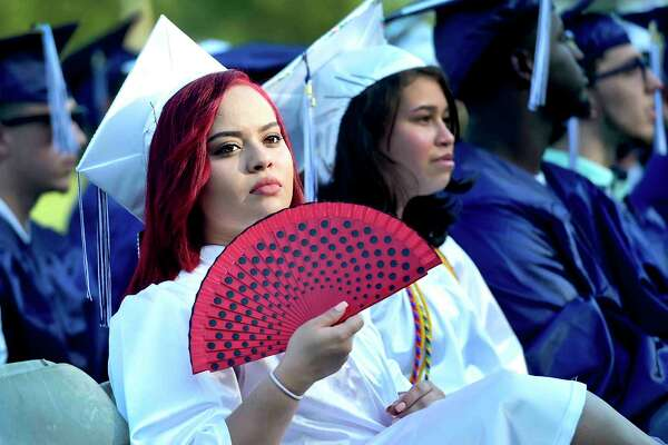 Graduate Aryanna Yveliz Torres keeps herself cool during the Ansonia High School Class of 2017 Commencement exercises at Jarvis Field in Ansonia, Conn. on Monday, June 12, 2017.
