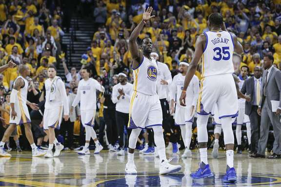 Golden State Warriors' Draymond Green and Kevin Durant go for a high five in the second quarter during Game 5 of the 2017 NBA Finals at Oracle Arena on Monday, June 12, 2017 in Oakland, Calif.