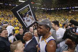 Golden State Warriors' Kevin Durant walks through the crowd after the Golden State Warriors defeated the Cleveland Cavaliers 129-120 during Game 5 to win the 2017 NBA Finals at Oracle Arena on Monday, June 12, 2017 in Oakland, Calif.