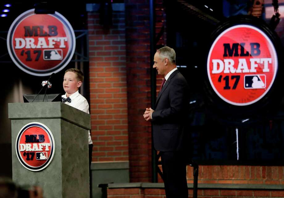 Landis Sims, left, a New York Yankees fan who was born without legs and hands, announces the Yankees selection in the first round of the Major League Baseball draft as commissioner Rob Manfred looks on, Monday, June 12, 2017, in Secaucus, N.J. (AP Photo/Julio Cortez) ORG XMIT: NJJC116 Photo: Julio Cortez / Copyright 2017 The Associated Press. All rights reserved.