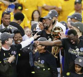 Golden State Warriors' Kevin Durant holds the the Larry O�Brien NBA Championship Trophy after the Golden State Warriors defeated the Cleveland Cavaliers 129-120 in Game 5 to win the 2017 NBA Finals at Oracle Arena on Monday, June 12, 2017 in Oakland, Calif.