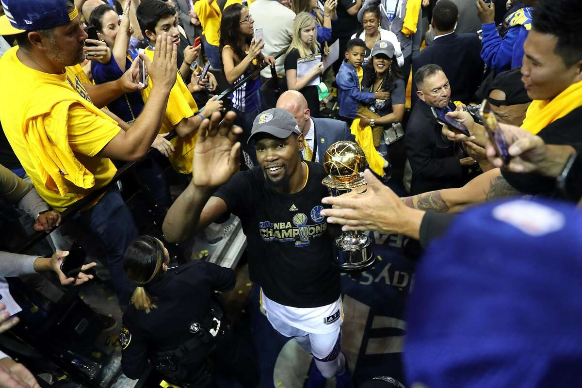Golden State Warriors' Kevin Durant carries the MVP trophy off the court after Warriors'129-120 win over Cleveland Cavaliers in Game 5 of NBA Finals at Oracle Arena in Oakland, Calif., on Monday, June 12, 2017.