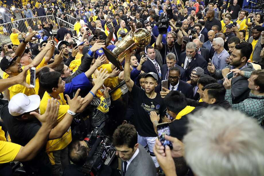 Golden State Warriors' Stepehn Curry carries the Larry O'Brien Trophy off the court after Warriors'129-120 win over  Cleveland Cavaliers in Game 5 of NBA Finals at Oracle Arena in Oakland, Calif., on Monday, June 12, 2017. Photo: Scott Strazzante, The Chronicle
