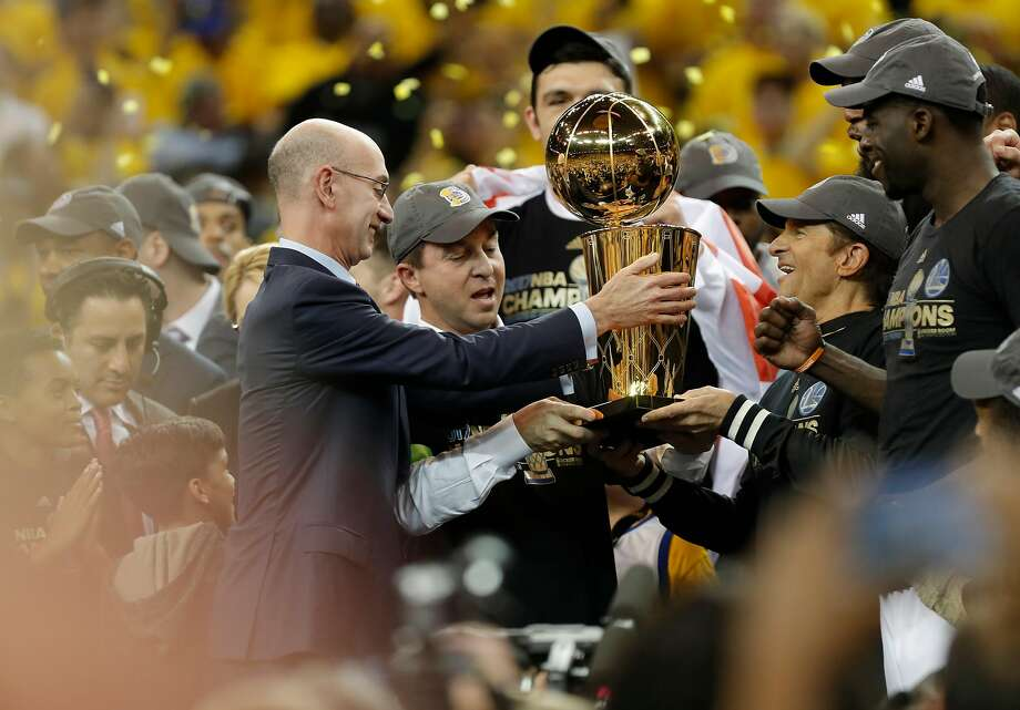 Commissioner Adam Silver presents the championship trophy to Joe Lacob and Peter Guber as the Golden State Warriors beat the Cleveland Cavaliers 129-120 in game 5 of the NBA finals to win the NBA championship at Oracle Arena in Oakland, Ca., on Monday June 12, 2017. Photo: Michael Macor, The Chronicle