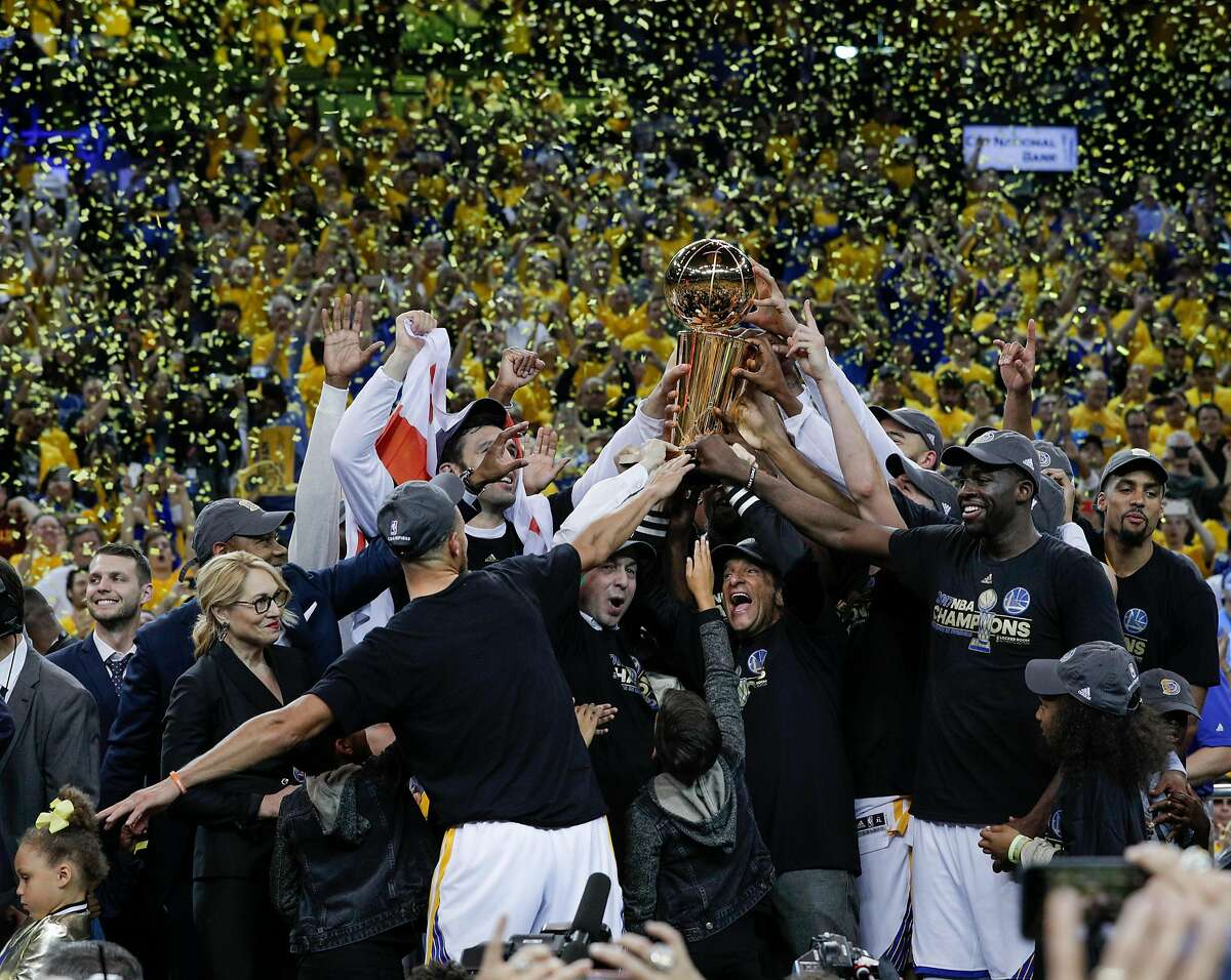 Golden State Warriors' owner Joe Lacob and executive chairman hold up the the Larry O'Brien NBA Championship Trophy after the Golden State Warriors defeated the Cleveland Cavaliers 129-120 in Game 5 to win the 2017 NBA Finals at Oracle Arena on Monday, June 12, 2017 in Oakland, Calif.