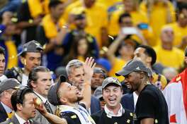 Golden State Warriors' Stephen Curry and Kevin Durant celebrate after the Golden State Warriors defeated the Cleveland Cavaliers 129-120 in Game 5 to win the 2017 NBA Finals at Oracle Arena on Monday, June 12, 2017 in Oakland, Calif.