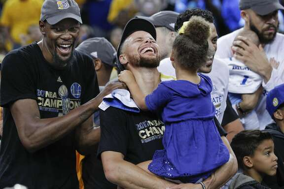 Golden State Warriors' Kevin Durant and Stephen Curry laugh while celebrating the Golden State Warriors win over the Cleveland Cavaliers in the 2017 NBA Finals at Oracle Arena on Monday, June 12, 2017 in Oakland, Calif.