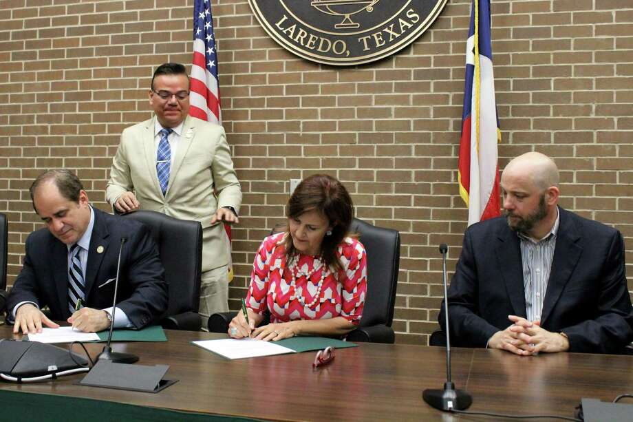 "Laredo Community College and Laredo Theater Guild International are teaming up to enhance the arts in Laredo. LCC President Dr. Ricardo J. Solis (seated, left) and LTGI Board President Linda Howland (center) signed a memorandum of understanding on Thursday with the goal of establishing a collaborative effort between the two groups to benefit academics and boost interest in theater and the arts within the community. The first production to be made under this agreement will be a performance of ""Beauty and the Beast,"" which will be held in the Guadalupe and Lilia Martinez Fine Arts Center theater July 13-16 and July 20-23. Joining Solis and Howland at the ceremony were LCC Executive Director of Economic Development & External Affairs Rodney Rodriguez (standing) and Chris Morgan of LTGI (far right). Photo: Courtesy /LCC"