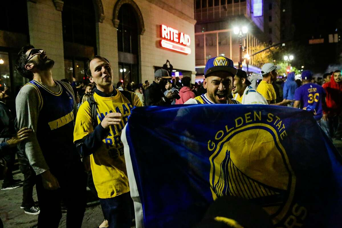 Golden State Warriors fan Dino Graniello (right) takes to the streets with other fans to celebrate their NBA Championship win against the Cleveland Cavaliers in Oakland, California, on Monday, June 12, 2017.