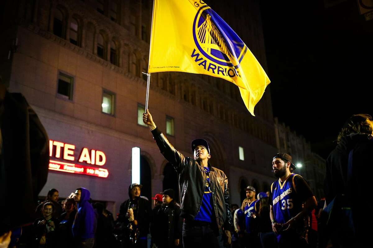 Golden State Warriors fan Ivan Chavarria waves a flag as he gathers with other fans at 14th Street and Broadway Street to celebrate the Warriors NBA Championship win against the Cleveland Cavaliers in Oakland, California, on Monday, June 12, 2017.
