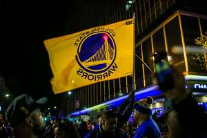 Golden State Warriors fans gather at 14th Street and Broadway Street to celebrate the Warriors NBA Championship win against the Cleveland Cavaliers in Oakland, California, on Monday, June 12, 2017.