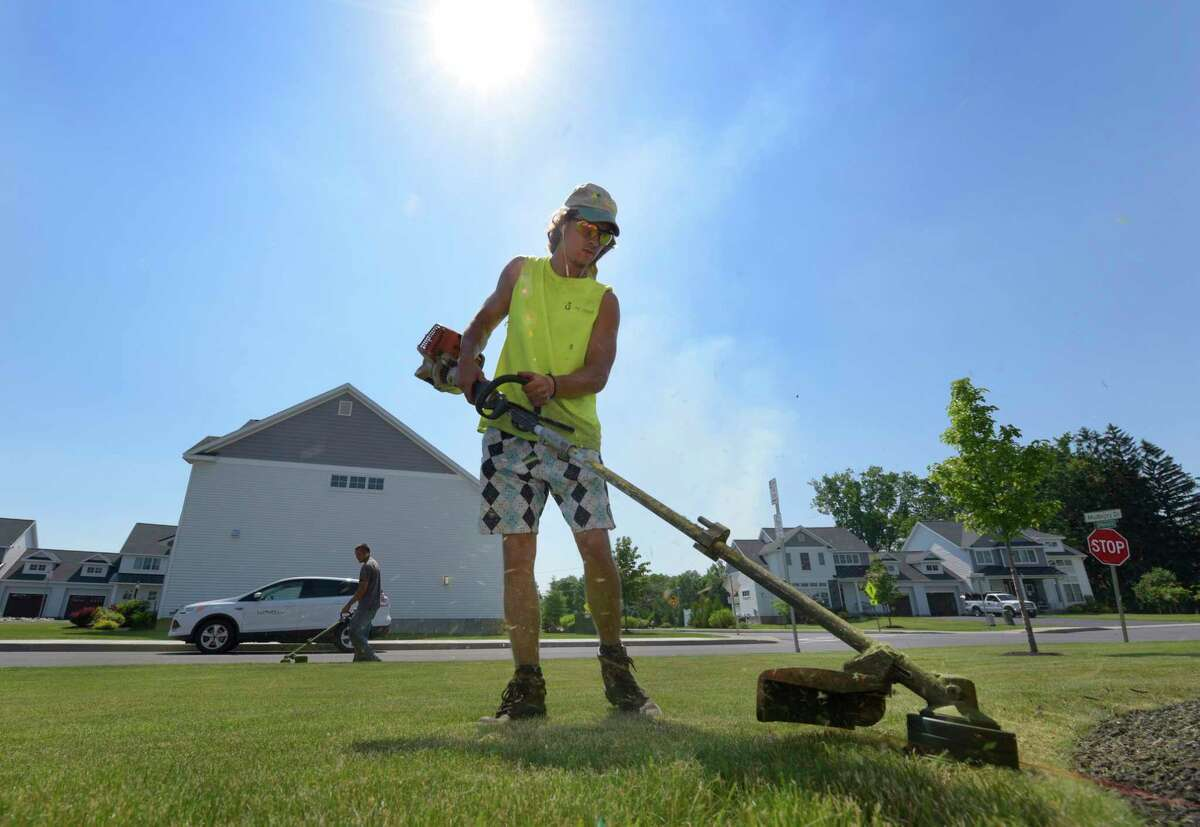 Jeff Wates, foreground, and foreman Mike Livingston, background, with All Good Companies, trim grass under the hot sun on Monday, June 12, 2017, in Albany, N.Y. (Paul Buckowski / Times Union)