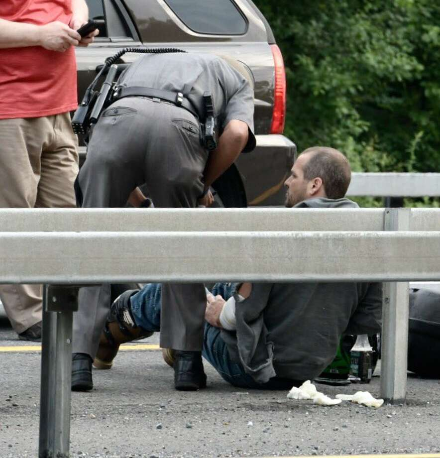 A motorcyclist is checked on by a state trooper after a wreck on the southbound side of Interstate 787 between exits 5 and 6. Photo: Skip Dickstein / Times Union