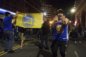 Golden State Warriors fans celebrate the team's NBA championship on the streets of Oakland on Monday night, June 12, 2017.
