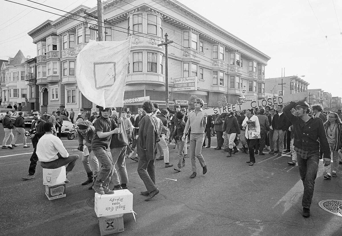 FILE - In this April 3, 1967 file photo, people parade up and down the streets of the Haight-Ashbury district in San Francisco. They came for the music, the mind-bending drugs, to resist the Vietnam War and 1960s American orthodoxy, or simply to escape summer boredom. And they left an enduring legacy. Fifty years ago, throngs of American youth descended on San Francisco to join a cultural revolution.