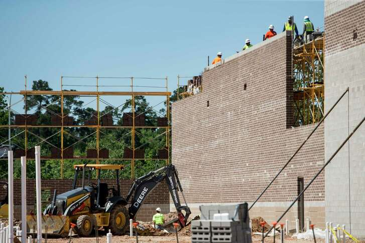 Workers build a portion of 336 Market-place in the Grand Central  Park  develop- ment in Conroe.