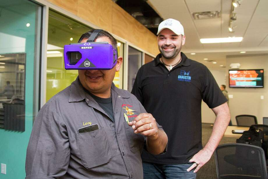 """Leroy Chavez, a client of Braustin Mobile Homes, """"tours"""" his future home using a pair of virtual reality goggles at the Geekdom office space in downtown San Antonio, while company President Alberto Piña watches. The company makes most of its sales online and over the phone. Photo: Alma E. Hernandez /For The San Antonio Express-News"""