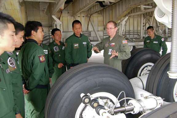 Maj. Chris Garnett, second from right, C-5A Galaxy pilot, explains the jet's complex landing-gear system to visiting pi'ots from the Defense Language Institute-English Language Center at Joint Base San Antonio-Lackland.