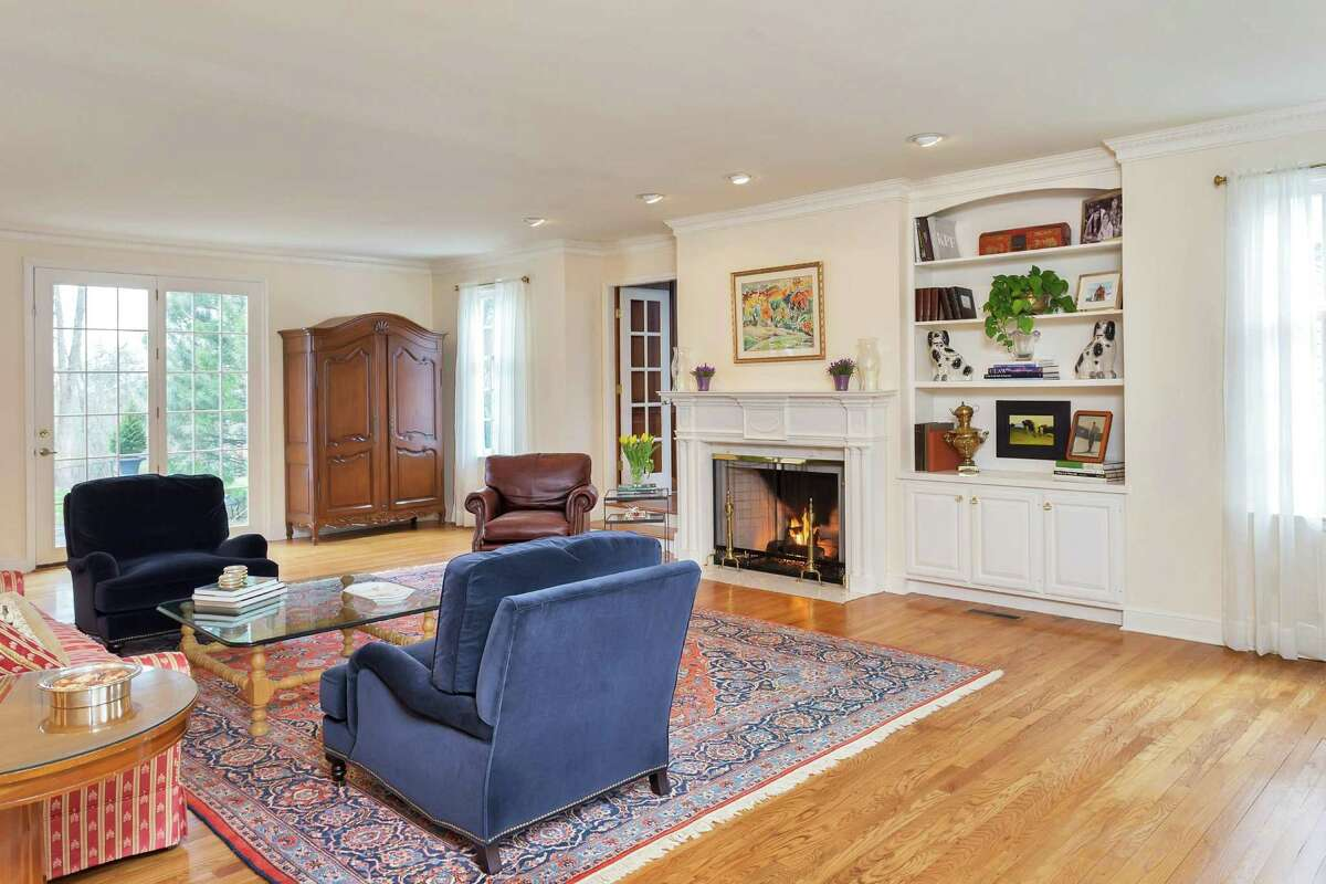 The spacious front-to-back formal living room has a marble gas fireplace with a decorative mantel, built-in shelving, and egg and dart crown molding.