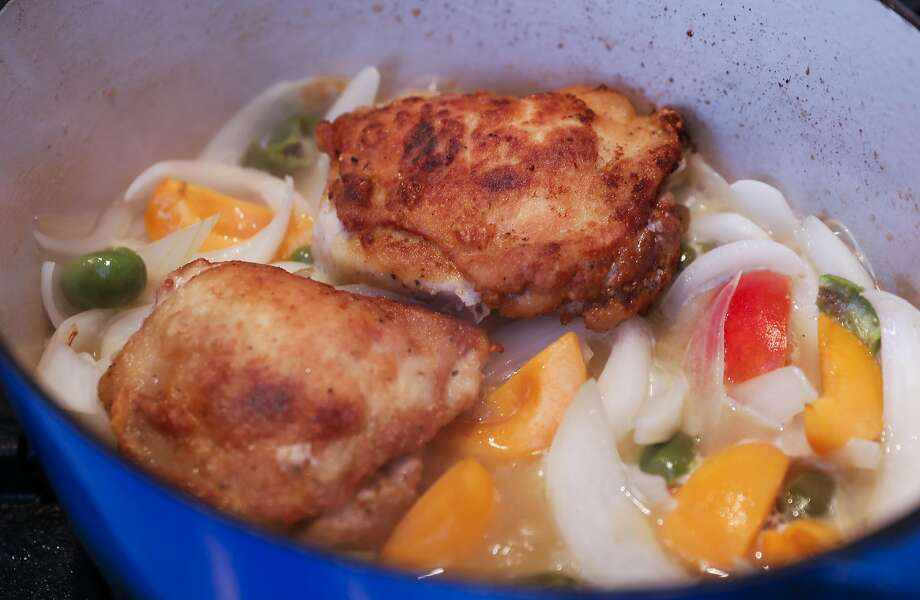 The chicken cooks with the onions, apricots, green olives and more. Photo: Russell Yip, The Chronicle
