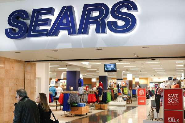 FILE - In this Wednesday, March 22, 2017, file photo, shoppers pass a Sears department store at the Tri-County Mall, in Springdale, Ohio. On Tuesday, June 13, 2017, Sears Holdings said it will cut about 400 full-time jobs as part of the troubled retailer�s plan to turn its business around. (AP Photo/John Minchillo, File)
