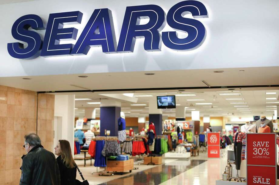 Shoppers pass a Sears department store at the Tri-County Mall, in Springdale, Ohio. On Tuesday, Sears Holdings said it will cut about 400 full-time jobs as part of the troubled retailers plan to turn its business around. Photo: John Minchillo /Associated Press / AP
