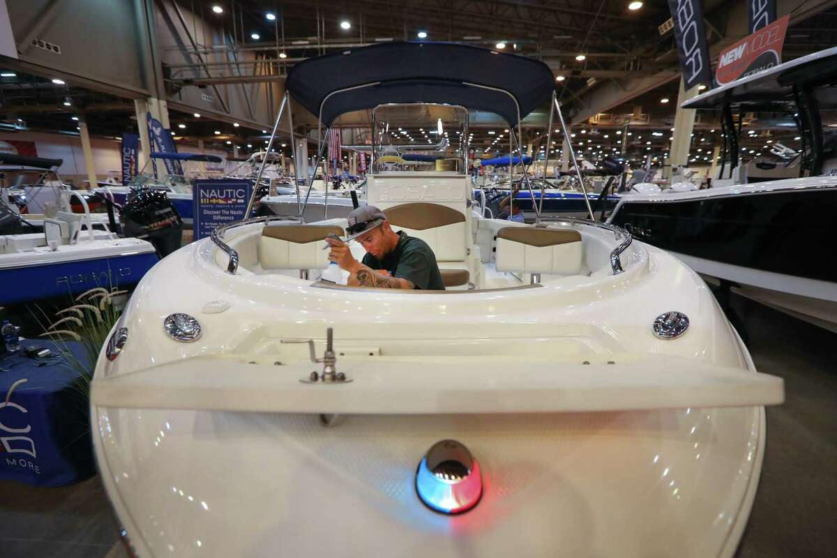Greg Francium polishes a Robalo R222 as dealers set up their displays before the opening of the Houston Summer Boat Show.