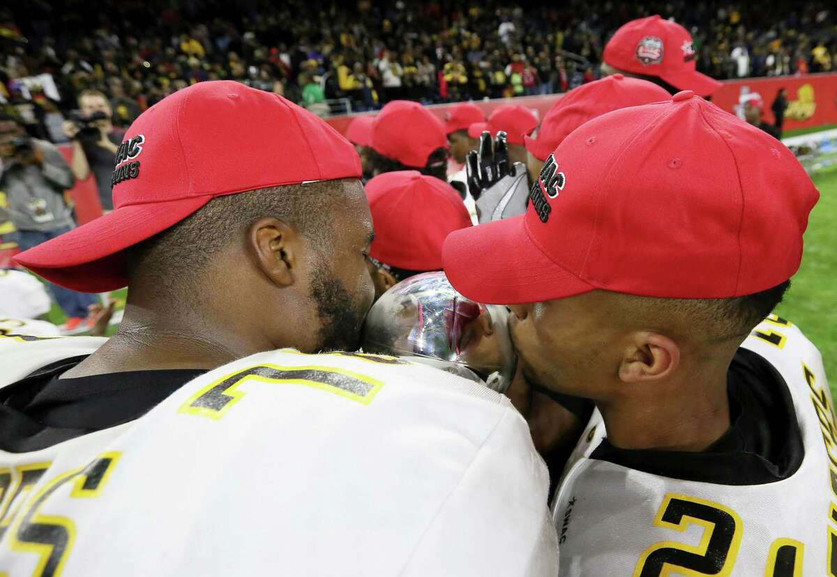 Grambling State University's Trent Scott, left, and Tyler Oliver kiss the Southwestern Athletic Conference Championship trophy after defeating Alcorn State University at NRG Stadium Saturday, Dec. 3, 2016, in Houston. The Tigers defeated the Braves 27-20. ( Yi-Chin Lee / Houston Chronicle )