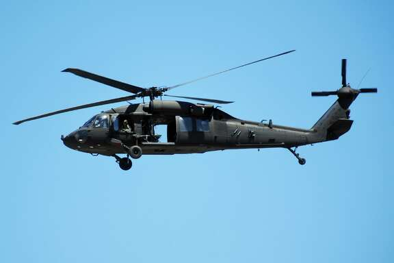 A Sikorsky UH-60 Black Hawk helicopter belonging to the Rhode Island Army National Guard flies over Quonset State Airport, in North Kingston, RI on June.